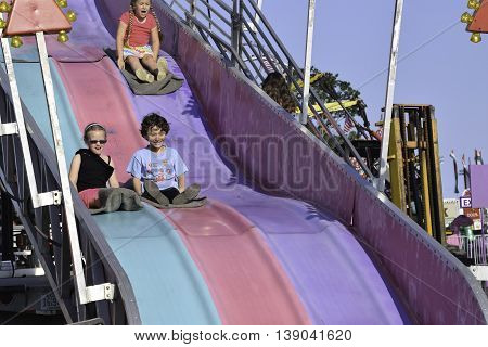 Wall Township NJ USA June 29 2014. Kids riding down a large colorful sliding board on fairgrounds in Wall Township NJ. Editorial use only.