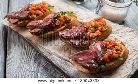 Sandwiches with cooked meat. Mixture of chopped vegetables. Delicious bruschetta with veal. Savoury snack on wooden board.