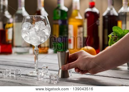 Wineglass with ice and jigger. Male hand with bar jigger. Tool of bartender. Choose ingredients for your cocktail.