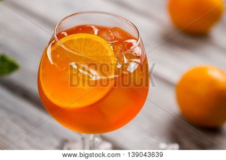 Orange drink in a wineglass. Ice and slice of orange. Aperol spritz with imported wine. Have fun at the party.