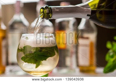 Bottle pours liquid in glass. Drink with mint leaves. Hugo cocktail prepared at bar. Mineral water and champagne.
