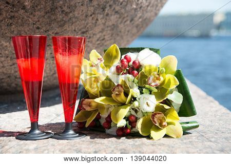 Wedding Bouquet Of Orchids And Two Red Glass Of Champagne