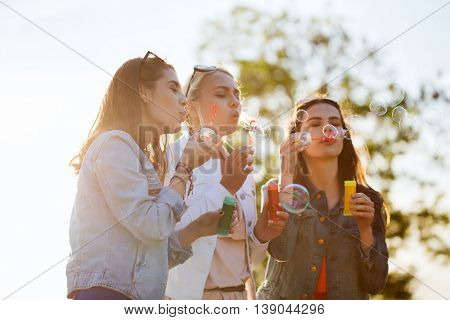 summer vacation, holidays, fun and people concept - group of happy young women or teenage girls blowing bubbles outdoors