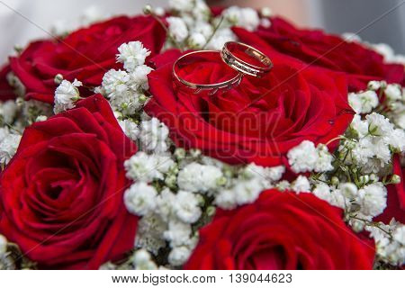 Engagement Rings And Bridal Bouquet Of Red Roses.