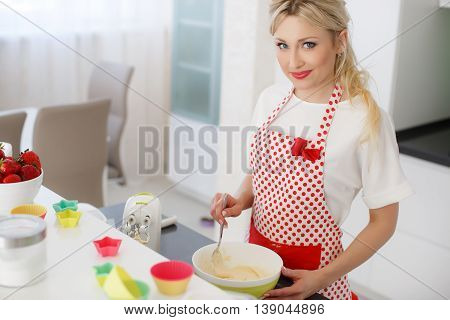 Young beautiful woman,blonde hair,light makeup and pink lipstick,nice smile,wears earrings,wears a white t-shirt and white red polka dot pinafore,engaged in the bright kitchen cooking baking