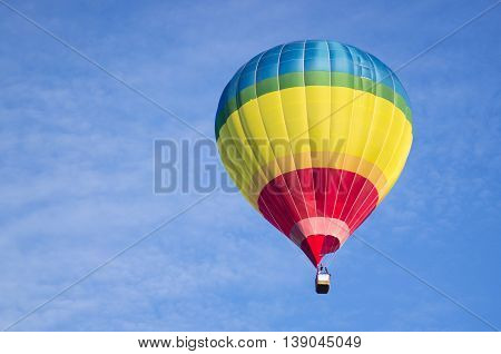 A colorful air balloon is floating in the blue sky.