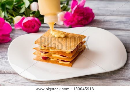 Bottle putting custard on shortcake. Pink flowers in the background. Ingredients for pastry. Dessert with sweet filling.