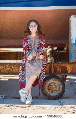 Cute teen girl, caucasian appearance, brunette with long curly hair, wearing sunglasses, wearing a long coat knitted red and blue, spending time in the countryside in the fresh air in summer, standing near a rusty truck for transportation of boats