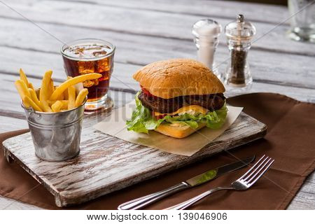 Bucket with fries and hamburger. Glass of cola with ice. Meal served in a cafe. Appetite has woken up.