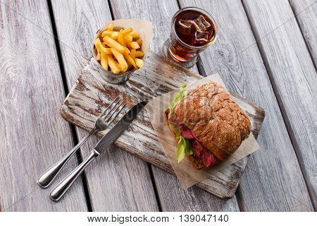 Fries and glass of cola. Sandwich and knife with fork. Meal in local bistro. Sandwich with veal and onion.