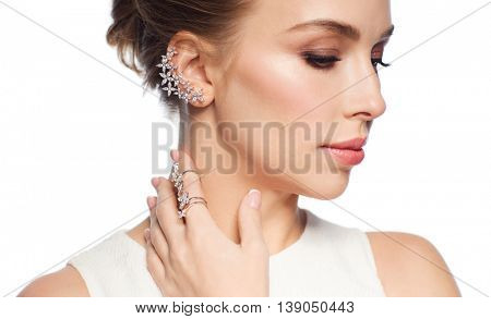 luxury, wedding and people concept - smiling woman in white dress with diamond jewelry over white background (focus on earring ang ring on finger)
