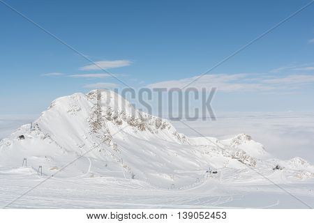 Mountain in the Dachstein area shines in the sunlight above the fog - austria