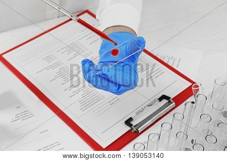 Doctor hands with glass pipette and microscope slides for blood sample