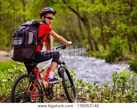 Bicycle girl. Girl with big rucksack rides bicycle. Girl cycling fording throught water . Cycling trip is good for health. Cyclist turned back.