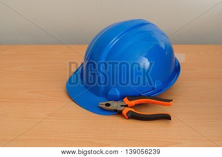 A blue hard hat displayed with a set of pliers