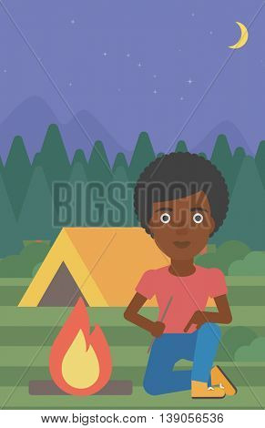 An african-american woman kindling campfire on the background of camping site with tent. Tourist relaxing near campfire. Woman sitting near campfire. Vector flat design illustration. Vertical layout.