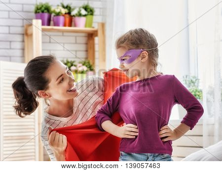 Happy family is preparing for a costume party. Mother and her child girl playing together. Girl in Superhero's costume.