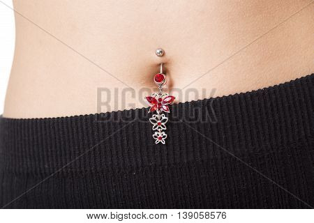 A Closeup of a belly button that is pierced with jewelry in it