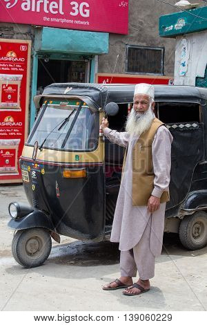 SRINAGAR INDIA - JULE 11 2015: Auto rickshaw taxis and muslim man on a road in Kashmir India. These iconic taxis have recently been fitted with CNG powered engines in an effort to reduce pollution
