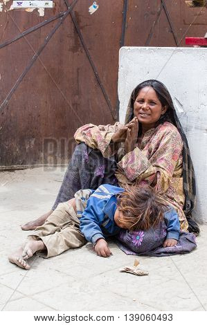 LEH INDIA - JUNE 24 2015: Unknown beggar woman with a child begging near Buddhist temple in Leh Ladakh. Poverty is a major issue in India