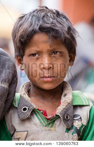 LEH INDIA - JUNE 21 2015: Unidentified beggar young boy on the street in Leh Ladakh. Poverty is a major issue in India