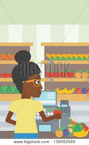 An african-american young female cashier standing at the checkout at the supermarket. Female cashier working at checkout at the supermarket. Vector flat design illustration. Vertical layout.