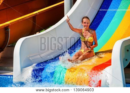 Wet child on water slide at aquapark shows thumb up on water slides with flowing water in water park. Summer water park holiday. Outdoor.