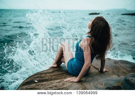 Young woman in a blue dress near the sea