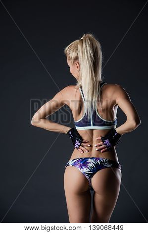 Dark contrast image of fitness woman's back and buttocks. She is training on black background in studio