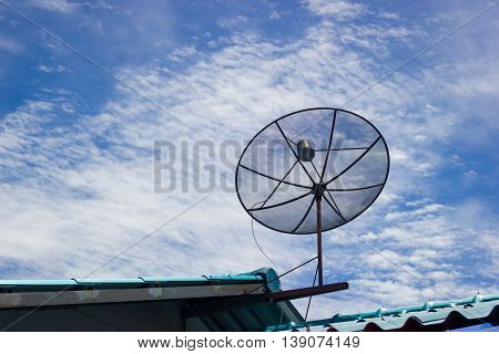 Satellite dish on the roof in the cloudy blue sky