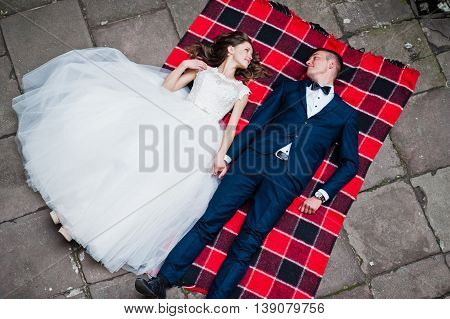 Wedding Couple Lying On Blankets. Photo From Quad Copter Drone View