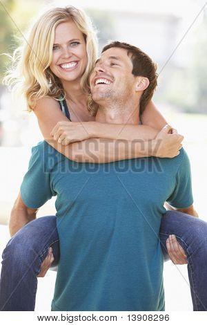 Young Man Giving Woman Piggyback Outdoors