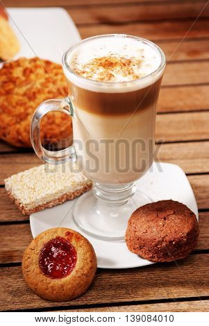 A delicius Capuchino coffe and little cookies