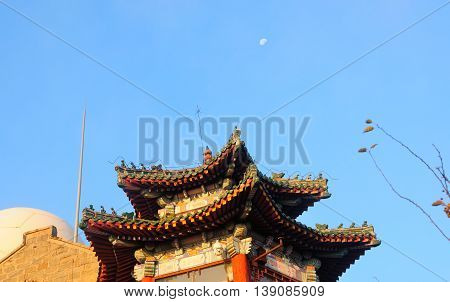 A Chinese style building under a waning moon in the morning sunlight on the top of Mount Tai (taishan) within the city of Tai'an located in Shandong province China.