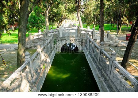 Cypress trees lining a water canal and chinese style stone bridge within the Confucius Temple in the city of Qufu in Shandong Province China.