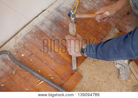 Workman removing old floor tiles using a hammer and chisel. Close up view of his gloved hands