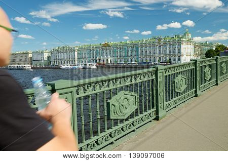 Man walking on a bridge across the river.In his hand a bottle of water from thirst.