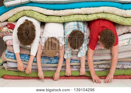 Kids laying inside the pile of mattresses and having fun. slumber party. funny activities with children indoors.