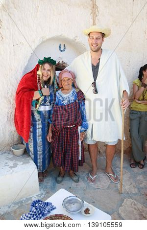 MATMATA TUNISIA - SEPTEMBER 17 2012 : Couple dressed in a berber's clothing with a berber woman in front of a troglodyte home tasting local food specialties in berber village in Matmata Tunisia.
