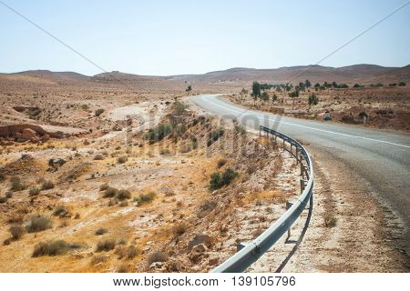 A road passing through the rocky desert of Matmata in south Tunisia. Matmata is famous for its troglodyte cave dwellings.