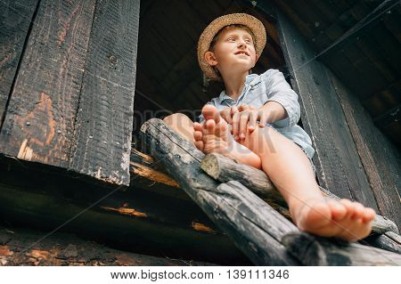 Barefoot boy sits on ladder in barn attic