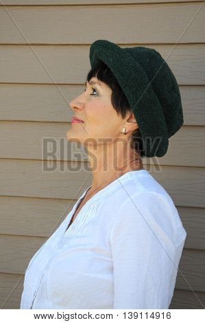Mature female senior beauty expressions against a wall outside.