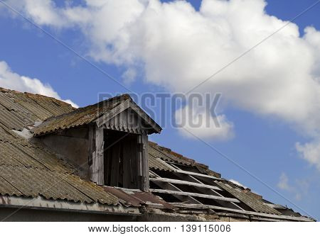 Old tile roof with holes and blue sky with clouds in sun day