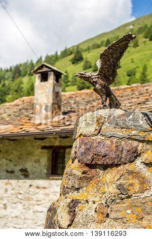 Bronze eagle statue on a rock in Ponte di Legno Italy