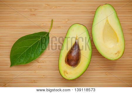 Healthy Food Concept. Closeup Ripe Avocado With Avocado Leaves On Wooden Background. Halved Organic