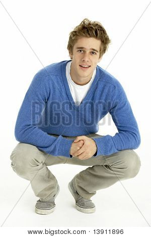 Young Man Crouching In Studio