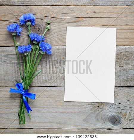 Bouquet of blue cornflowers and blank greeting card on wooden background