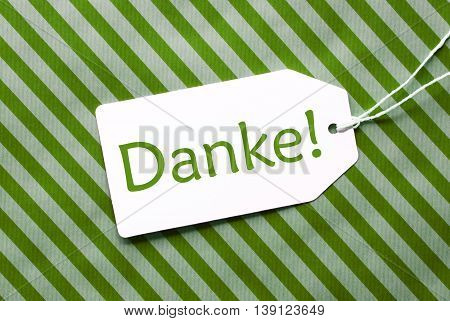 One Label On A Green Striped Wrapping Paper. Textured Background. Tag With Ribbon. German Text Danke Means Thank You