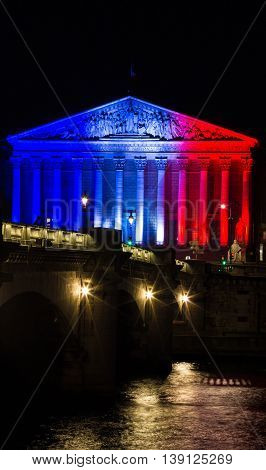 Paris France-July 18 2016 : The French National Assembly lit up with colors of French national flag to honor the victims of July 14 2016 terrorist's attack in Nice.