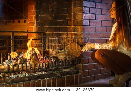 Woman At Home Fireplace Making Fire With Bellows.